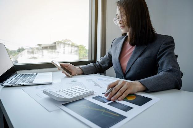 Бухгалтер бизнес-леди использует смартфон и ноутбук, делая счет для уплаты налогов на белом столе в рабочем офисе.