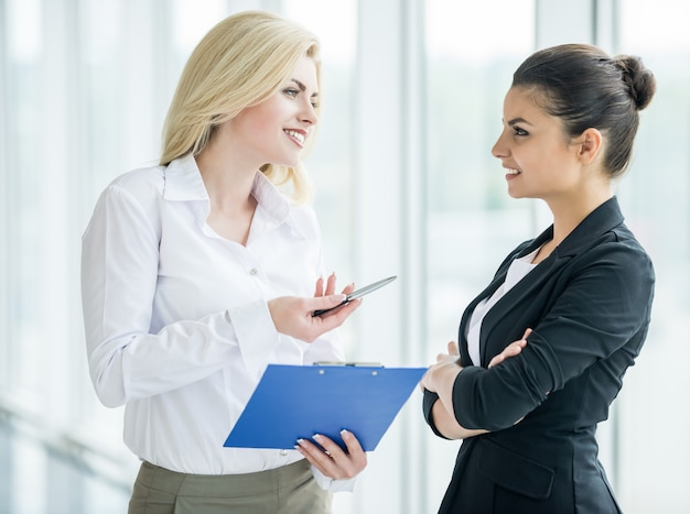 Businesswomen dressed formal discuss project at office.
