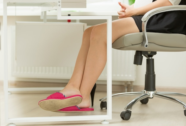 Businesswomen feet in slippers under office table