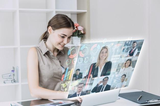Деловые женщины с удовольствием используют высокотехнологичные онлайн-встречи через интернет с футуристическим цифровым устройством для видеосвязи с деловыми партнерами по всему миру в концепции офиса.
