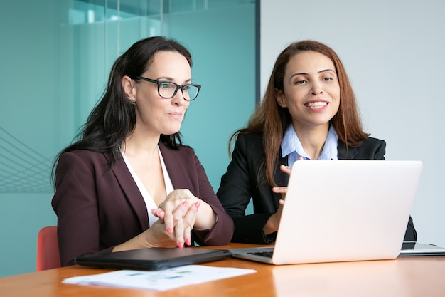 Businesswomen having video talk to partners, sitting at open laptop, looking at display and smiling