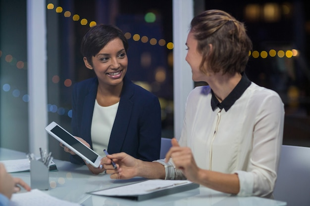 Businesswomen interacting with each other in conference room