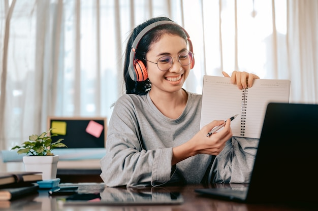 Businesswomen is using notebook computers and wear headphones for online meetings and working