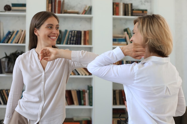 Businesswomen keep their distance because of covid-19 infection and greet each other with their elbows.