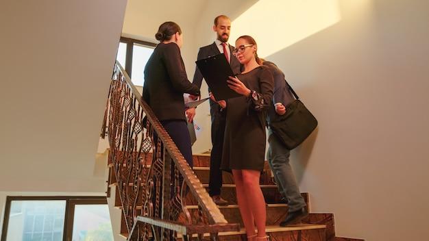 金融会社の階段で会うビジネスウーマンは、階段に立っているグラフを分析します。現代の金融ビルで働くプロの成功したビジネスマンのグループ