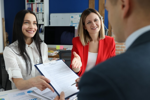 Businesswomen offering to sign contract to man in office