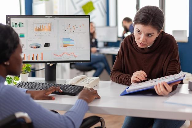 スタートアップ企業のオフィスで一緒に働くコンピューターを見て財務戦略を計画しているビジネスウーマン