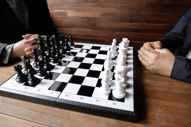 Businesswomen play chess on board challenges planning business strategy to success concept