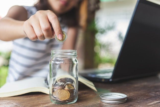 Businesswomen put the coin in a glass jar to save money, save money