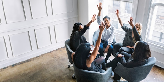 Businesswomen putting hands in the middle
