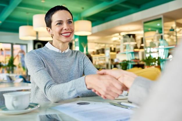 Businesswomen shaking hands in cafe meeting