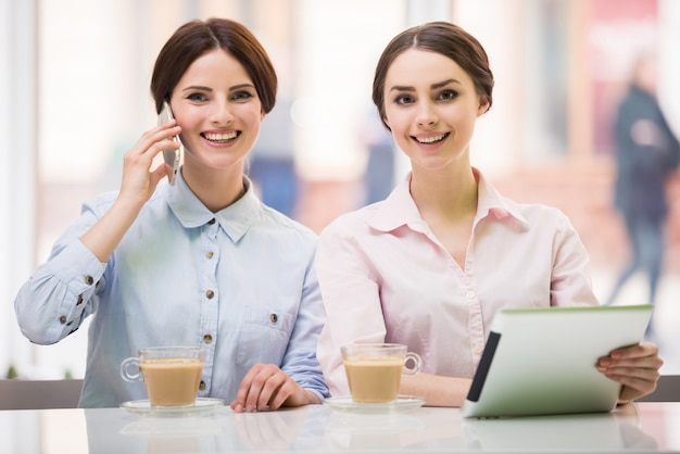 Businesswomen sitting in urban cafe and using digital tablet