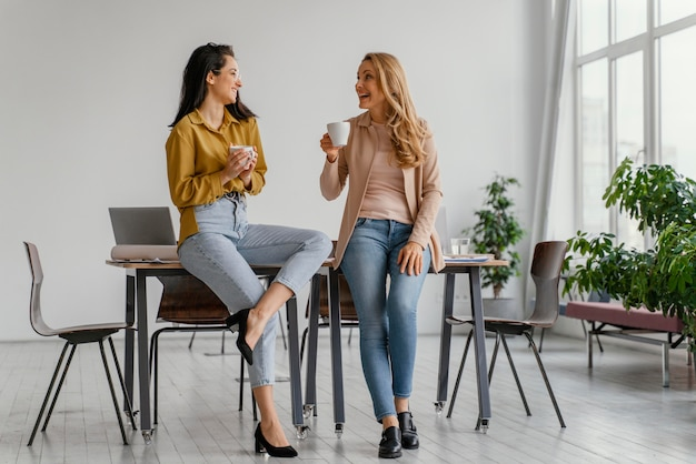 Businesswomen talking while enjoying a cup of coffee