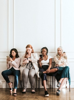 Businesswomen using digital devices while waiting