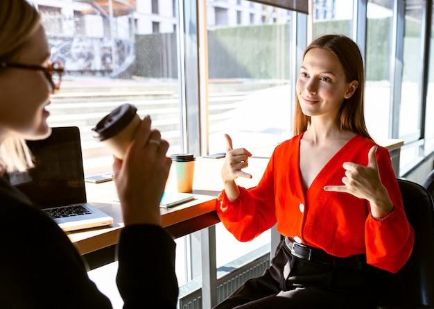 コーヒーを飲みながら仕事で手話を使用するビジネスウーマン