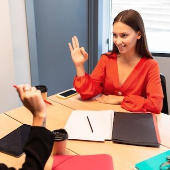 手話を使ってコミュニケーションをとるビジネスウーマン