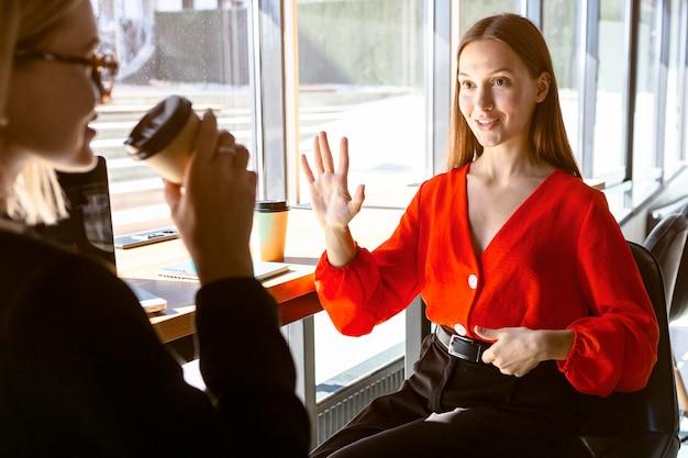 仕事でコーヒーを飲みながら手話を使用するビジネスウーマン
