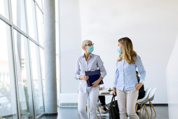 Деловая женщина гуляет в офисе и носит маску для защиты от вирусов