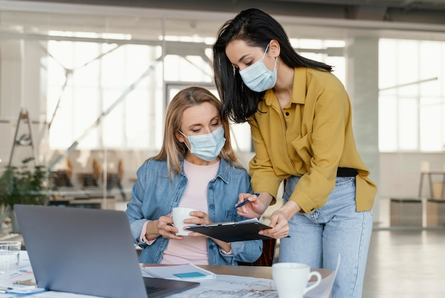 Donne di affari che indossano maschere mediche al lavoro