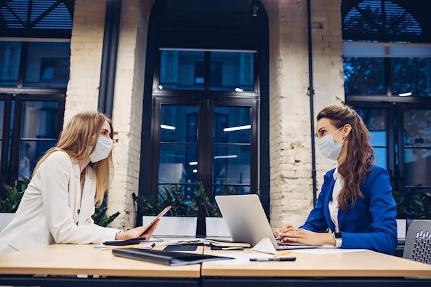 사무실에서 테이블에서 작업하는 의료 마스크를 착용하는 경제인