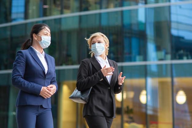 ビジネスウーマンがオフィススーツとマスクを着用し、会議を行い、市内で一緒に歩き、話し、プロジェクトについて話し合っています。ミディアムショット。流行コンセプト中のビジネス