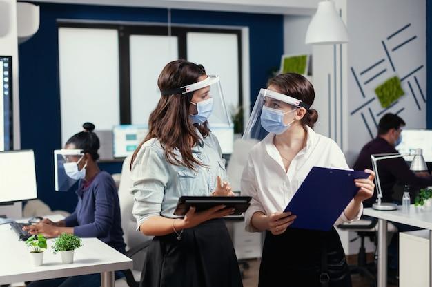 Donne d'affari con maschere di protezione contro il coronavirus in piedi sul posto di lavoro che parlano di dati finanziari aziendali in possesso di tablet digitale. team aziendale multietnico che lavora rispettando la distanza sociale
