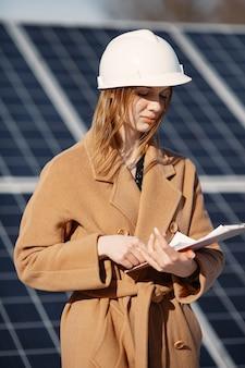 Imprenditrici che lavorano sul controllo delle apparecchiature presso la centrale solare. con elenco di controllo tablet, donna che lavora all'aperto a energia solare.