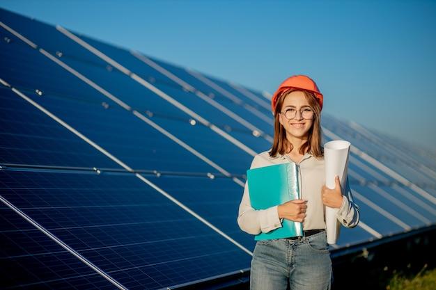 タブレットチェックリストで太陽光発電所で機器のチェックに取り組んでいるビジネスウーマン、太陽光発電所で屋外で働いている女性。