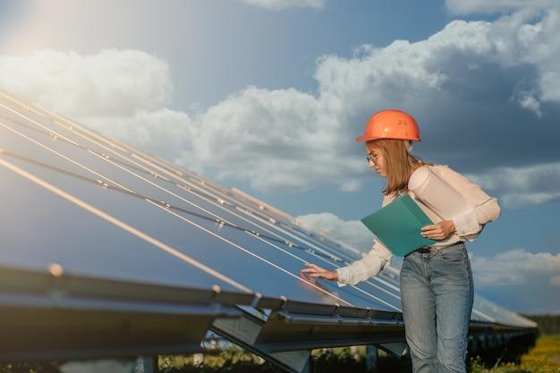 Деловые женщины, работающие на проверке оборудования на солнечной электростанции с контрольным списком планшета, женщина, работающая на открытом воздухе на солнечной электростанции.