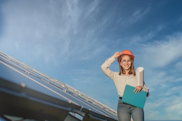 タブレットチェックリストを使用して太陽光発電所で機器のチェックに取り組んでいるビジネスウーマン、太陽光発電所で屋外で働いている女性。