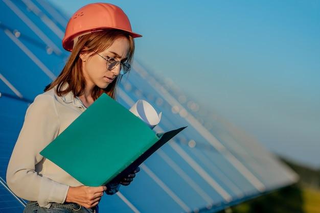 タブレットのチェックリストを使って太陽光発電所の機器をチェックするビジネスウーマン、太陽光発電所の屋外で働く女性。