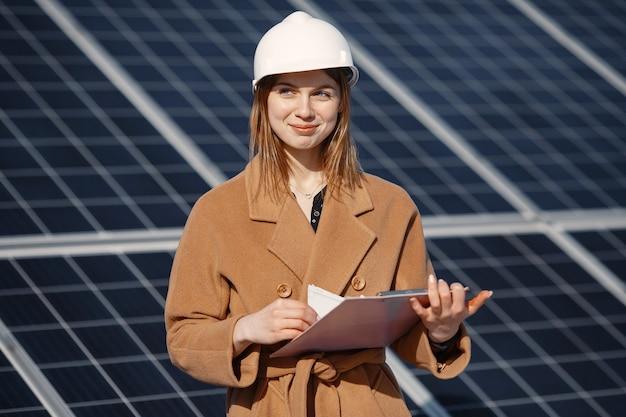 Деловые женщины работают над проверкой оборудования на солнечной электростанции. с контрольным списком планшета, женщина, работающая на открытом воздухе на солнечной энергии. Premium Фотографии