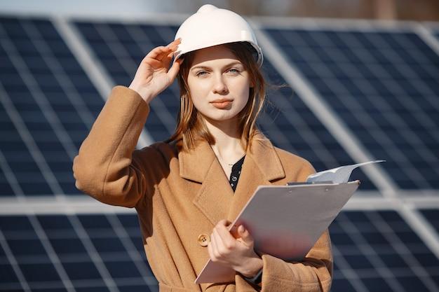 태양 광 발전소에서 장비 검사에 노력하는 경제인. 태블릿 체크리스트와 함께 태양 광 발전에서 야외에서 일하는 여성.