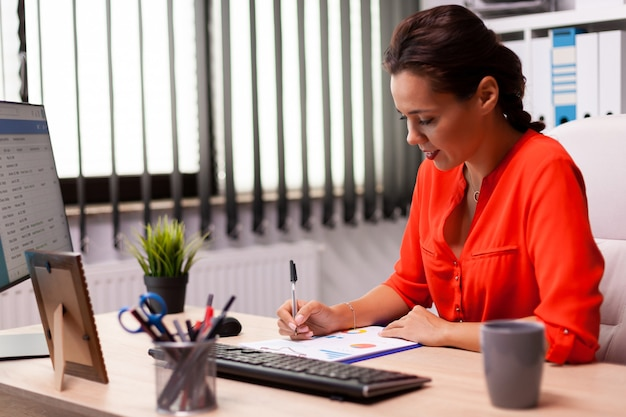 Businesswwoman entrepreneur writing financial sales on charts sitting at desk in workplace wearing red. successful financial auditor in data marteking looking at graphs on computer screen and writing