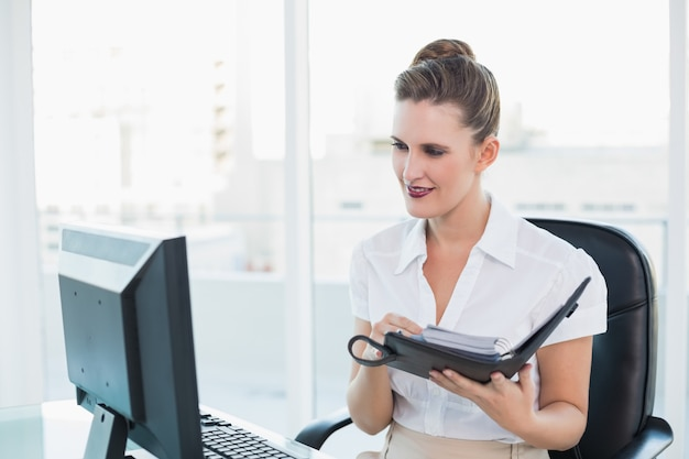 Businsswoman looking at computer screen while holding datebook