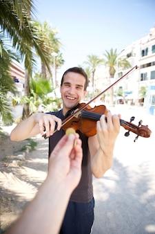 Баскер играет на скрипке снаружи за деньги