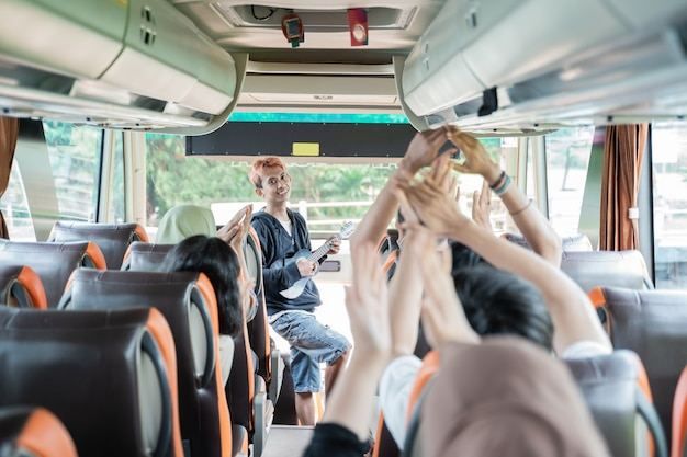 A busker using an ukulele musical instrument and bus passengers sing and clap their hands while traveling