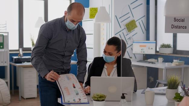 Covid19パンデミックの間に会社のオフィスでラップトップのマーケティングプロジェクトで働いている医療フェイスマスクを持つbussinesチーム。ウイルス病を回避するために社会的距離を保つ同僚