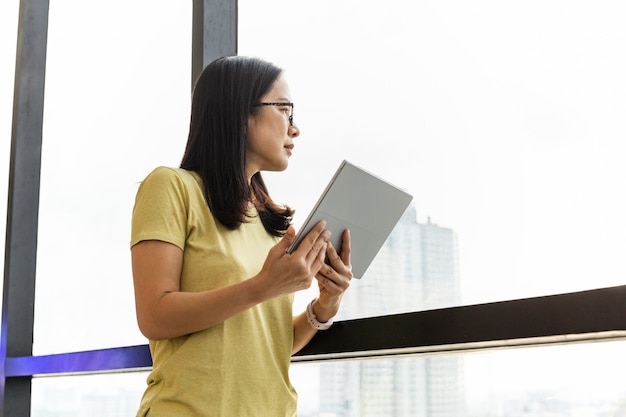 オフィスの窓の横に立っているタブレットを保持している黄色のtシャツを着たビジネスの女性