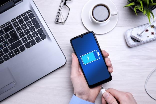 Рабочее место деревянного офисного стола bussines с пустым мобильным телефоном, различными принадлежностями. ставит телефон на зарядку.