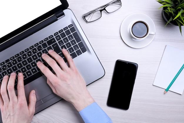 Рабочее место деревянного офисного стола bussines с пустым мобильным телефоном, различными принадлежностями. ноутбук, смартфон, чашка кофе