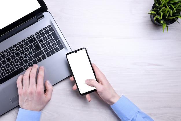 空白の携帯電話、さまざまな物資を備えたビジネス木製オフィスデスクの職場。モックアップ。ノートパソコン、スマートフォン、一杯のコーヒー