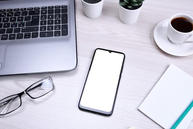 空白の携帯電話、さまざまな供給とbussines木製のオフィスデスクの職場。