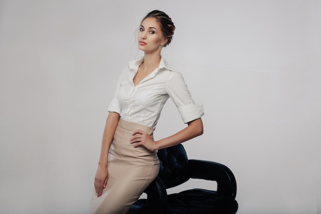 灰色の背景とスタジオの上に立って美しいエレガントな若いbussines女性