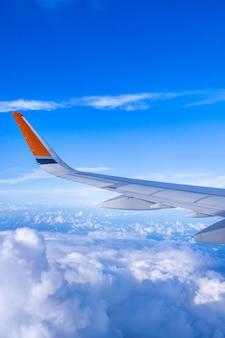 ビジネスと旅行のコンセプト。美しい青い空と日光の雲、コピースペース、上面図と航空機キャビン内の窓からの空中写真