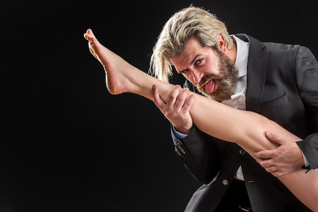 Bussiness male in suit with female legs. man with foot fetish lick leg. luxury and patriarchy.