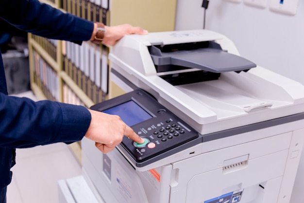 ビジネスマンハンドプレスボタン、プリンタースキャナーレーザーオフィスコピー機用品のパネル上のボタンを押すとコンセプトがスタートします。