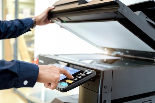 Деловой человек ручное нажатие кнопки на панели принтера