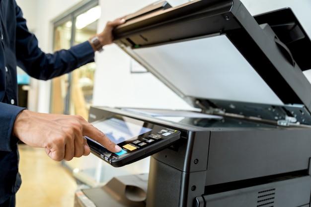 ビジネスマンの手はプリンターのパネルのボタンを押します。