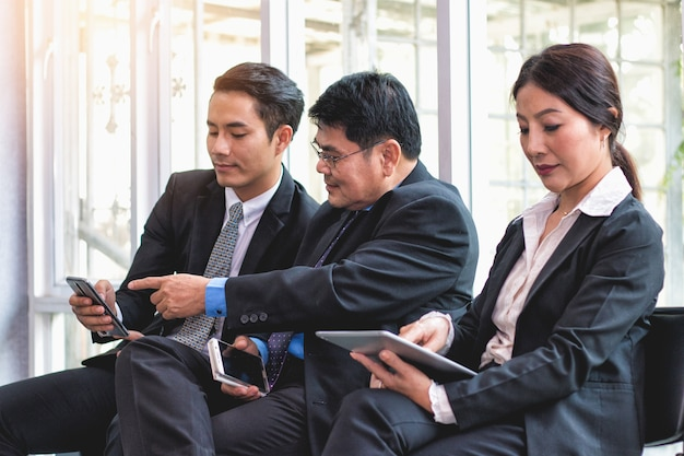 Бизнес-люди ищут и улыбаются контент на сотовый телефон